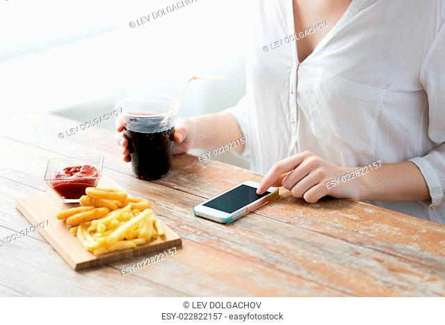 fast food, people, technology and diet concept - close up of woman with smartphone drinking cola and eating french fries