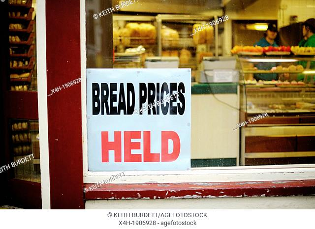 Sign announcing the holding of bread prices in a bakers window, Aberystwyth, Wales
