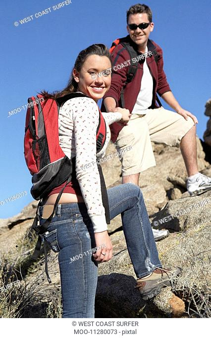 Young man helping young woman over rocks