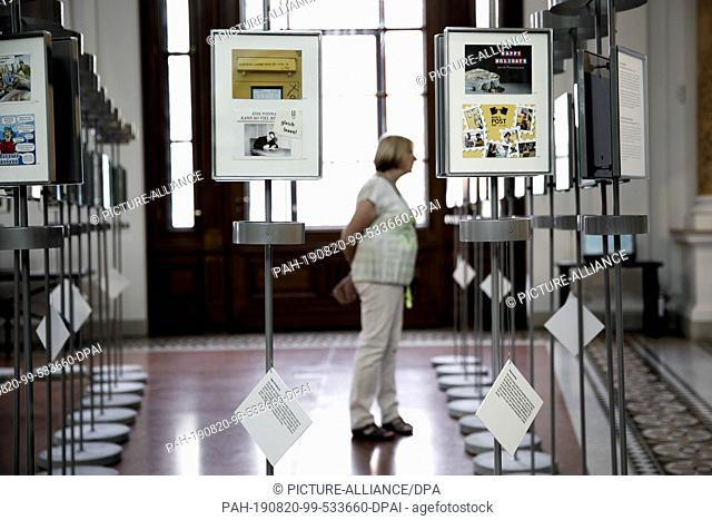 """20 August 2019, Berlin: A visitor looks at postcards on display in the anniversary exhibition """"""""More than words"""""""" at the Museum of Communication"""