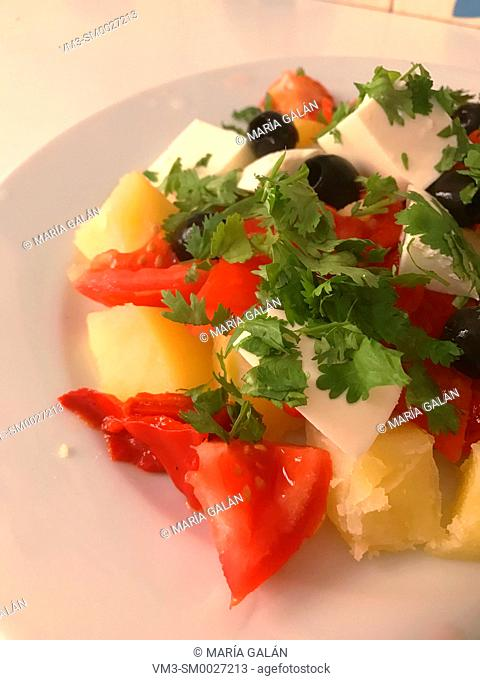 Salad made of potato, tomato, red pepper, cottage cheese, black olives, parsley and olive oil. Close view