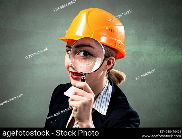 Professional appraiser looking through magnifying glass. Woman civil engineer in safety helmet checking with magnifier on wall background