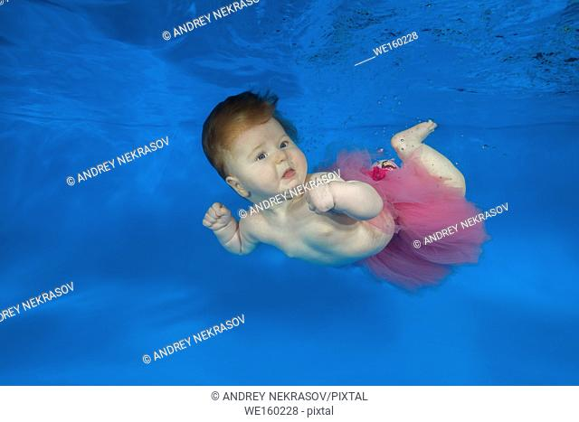 little girl swim underwater in the pool