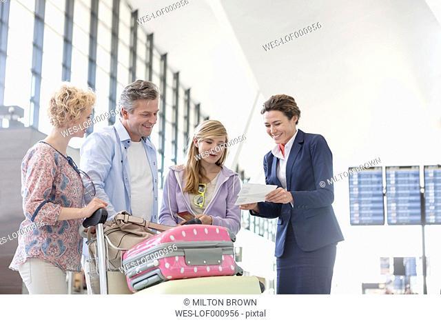 Flight attendant guiding family with flight tickets