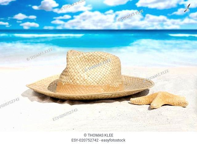 Strohhut und Seestern liegen am Sandstrand