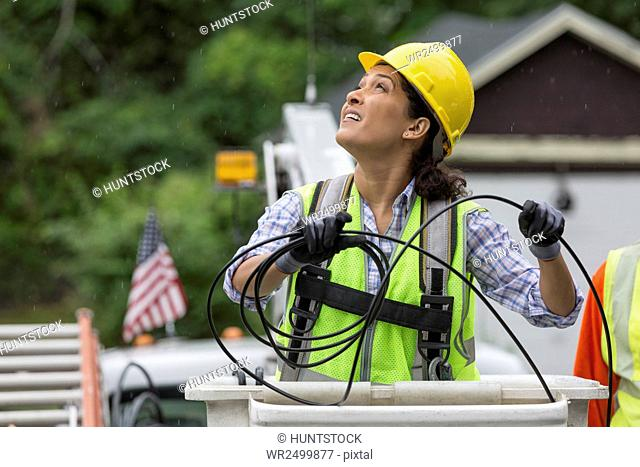Hispanic female cable lineman stringing a new line in the rain