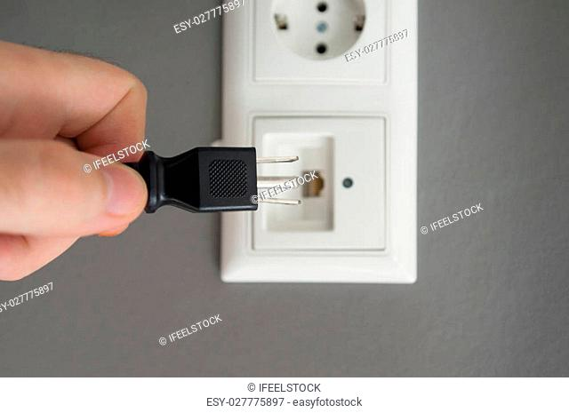 Male hand trying to plug an american type of plug to an internet outlet