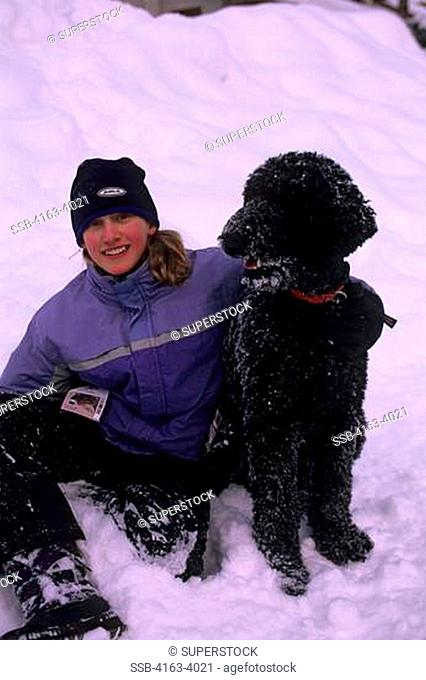 CANADA, BRITISH COLUMBIA, SUN PEAKS, VILLAGE SCENE, GIRL 11 YEARS OLD WITH POODLE IN SNOW