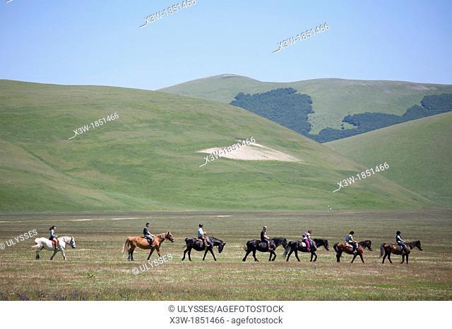 horsemen riding in open space, landscape, castelluccio di norcia, umbria, italy, europe
