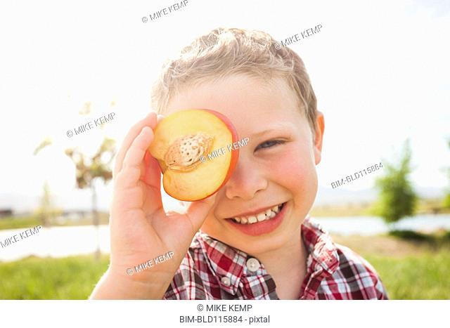 Caucasian boy holding fruit over eyes