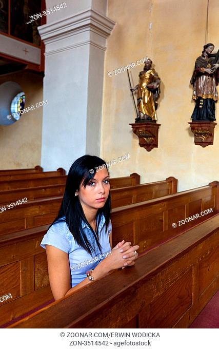 Junge Frau betet in einer Kirche