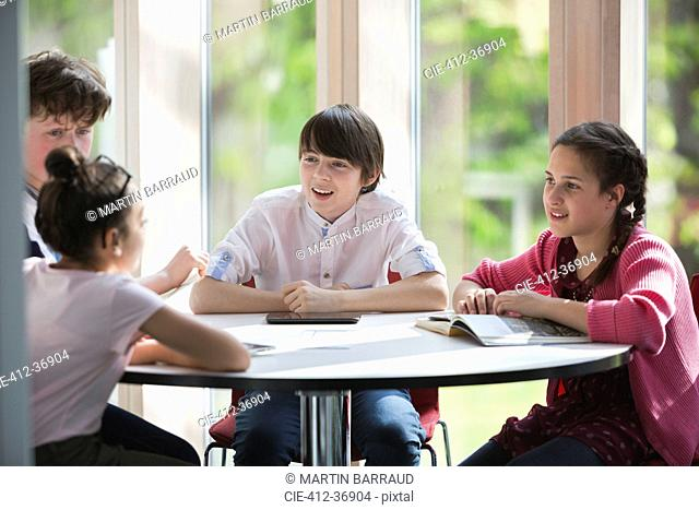 Students talking at table in library