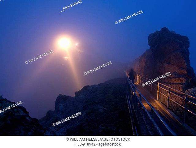 USA, California, Marin County, Point Reyes National Seashore, lighthouse and staircase in fog at dusk, person on stairs