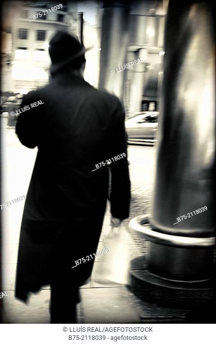 Rear view of a unrecognizable man walking down the street and talking on the phone in London, England, UK, Europe