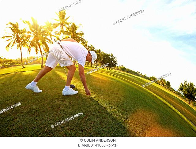 Fish eye view of Caucasian golfer teeing off on course