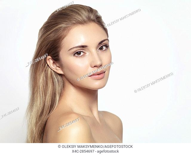Beauty portrait of a young beautiful woman face with long light brown blond hair, exotic sensual look and clean glowing skin isolated on white background