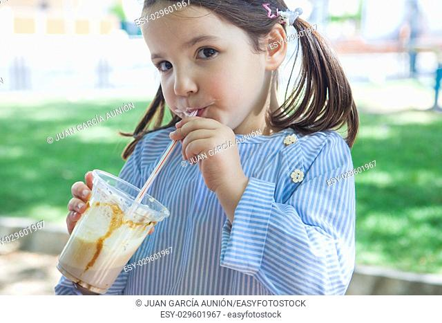 Little girl drinking milkshake at park. She is 5 years old