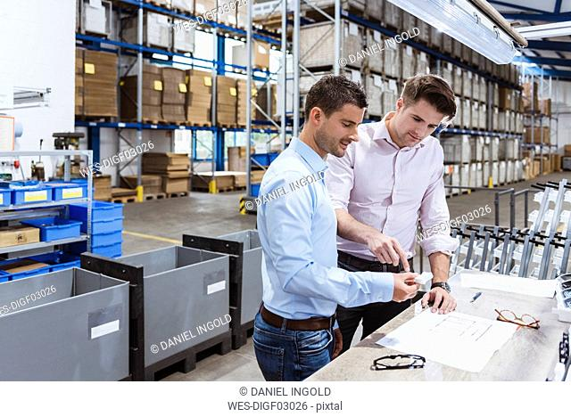 Business people standing on shop floor, discussing product improvement