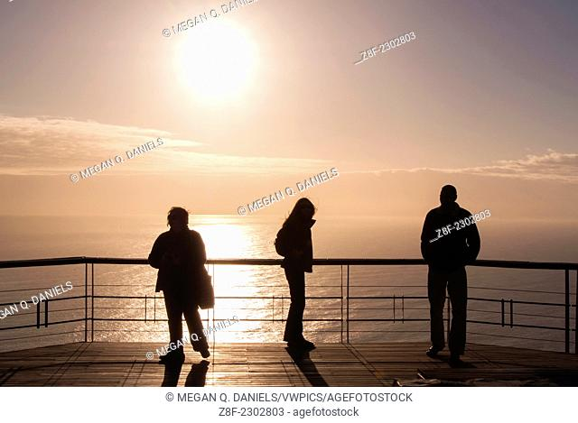 South African residents and tourists stand on a pier admiring the sunset on Signal Hill in Cape Town, South Africa overlooking the Atlantic Ocean