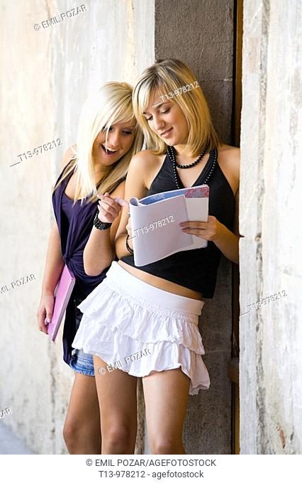 Two student young women with a paper notebook, one is surprised