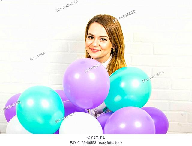 Young pretty woman with many colored balloons