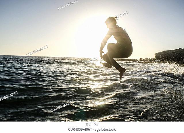 Teenage boy jumping in the sea