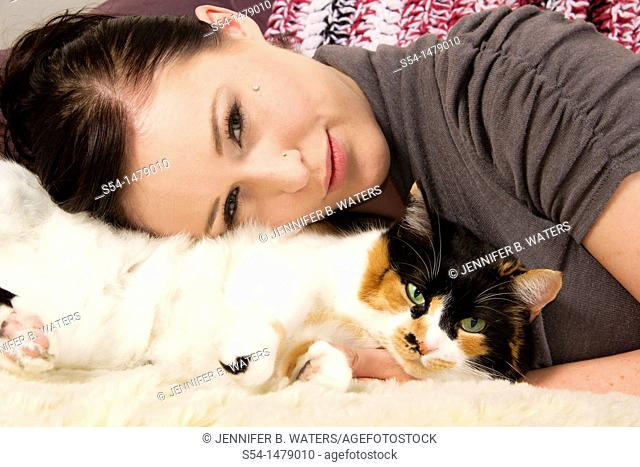 A young caucasian woman and her calico cat indoors