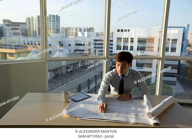 Singapore, Architect working on architectural plans in office
