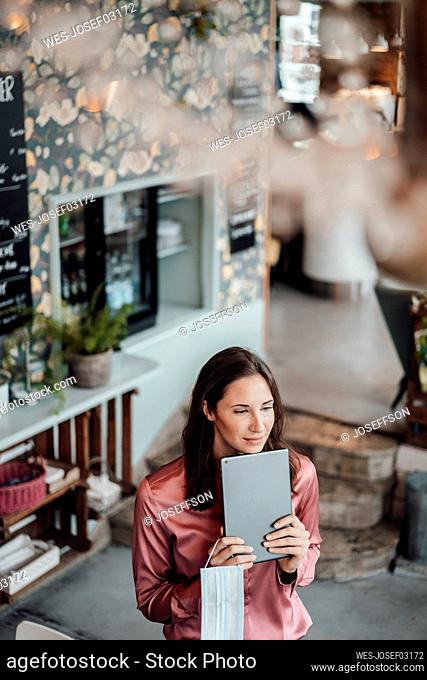 Businesswoman with digital tablet looking away in cafe during COVID-19