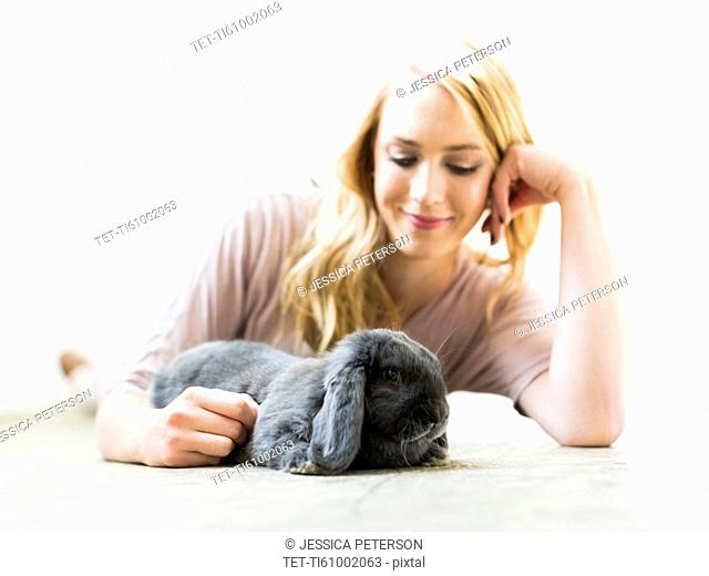 Young woman lying on floor and stroking rabbit