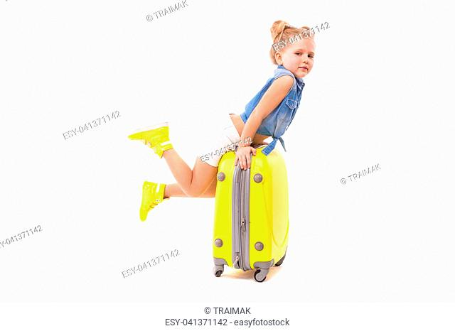 Isolated on white, beauty caucasian blonde girl in blue shirt, white shorts, sunglasses and yellow boots hang on the yellow suitcase, look at camera
