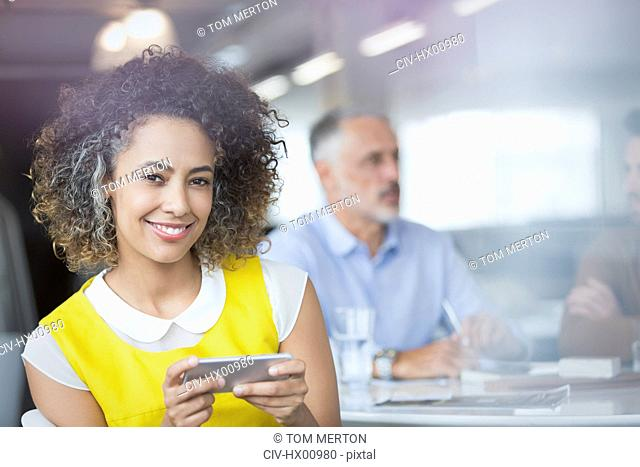 Portrait smiling businesswoman texting with cell phone in meeting