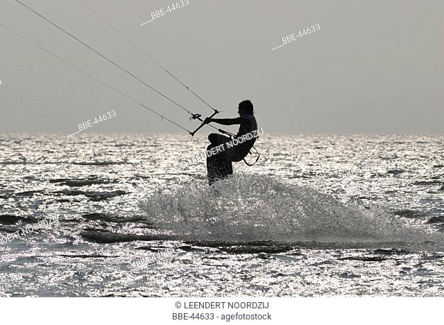 Kitesurfer in action in backlight