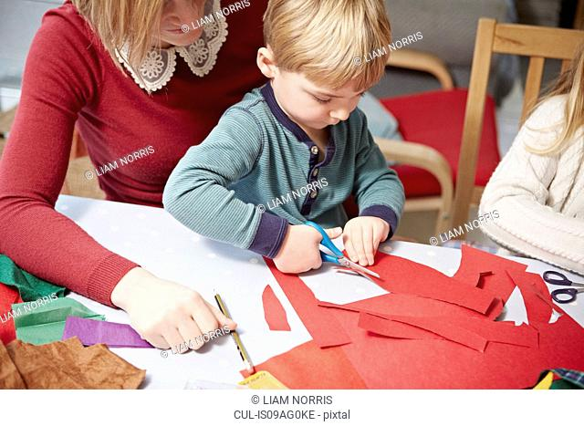 Mother and son craft making at kitchen table