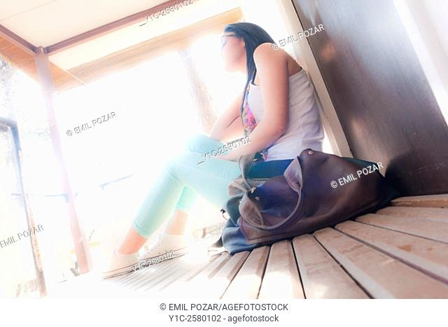 Student young woman sitting against bright sunlight