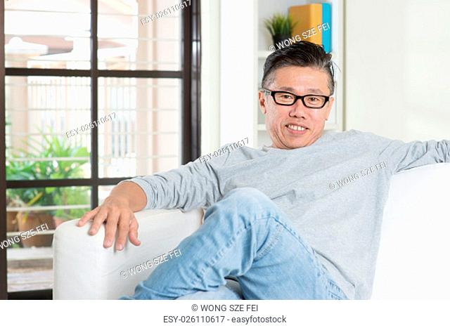 Portrait of mature 50s Asian man smiling and sitting at home. Senior Chinese male relaxed and seated on sofa indoor