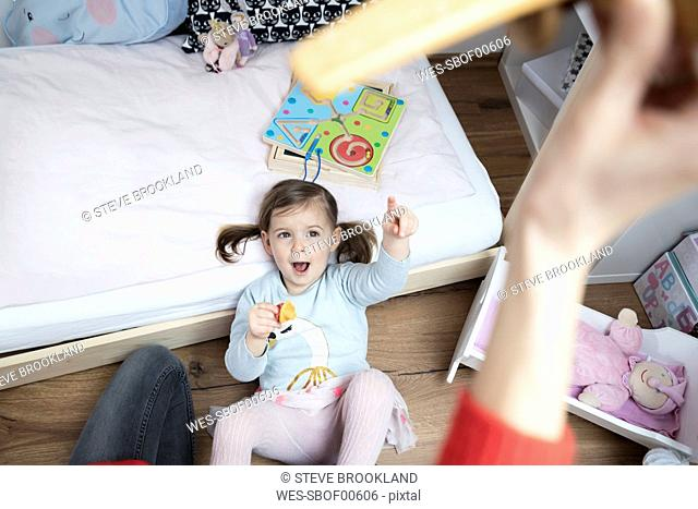 Toddler girl pointing at mother's hand holding a toy plane