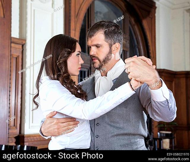 Confident mid adult man performing tango with beautiful woman in restaurant