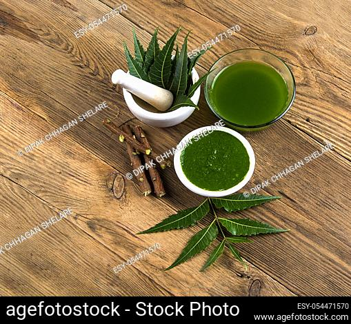 Medicinal Neem leaves in mortar and pestle with neem paste, juice and twigs on wooden background