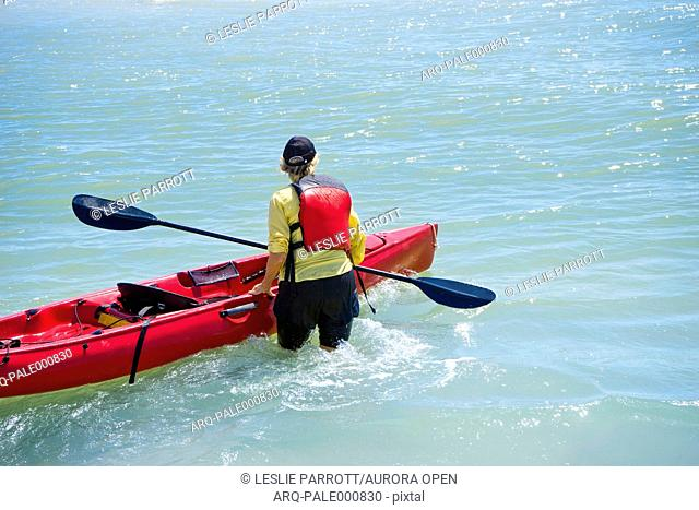 Woman wading in water with a kayak