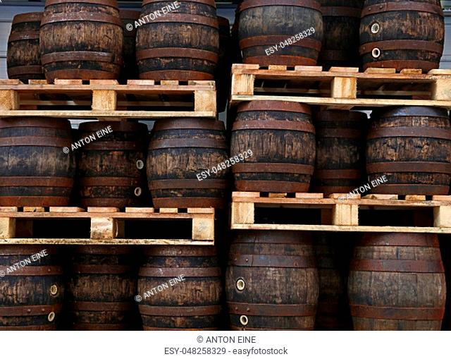 Rows of pallets with staked old grunge vintage dark oak wood barrels of craft beer at warehouse of brewery