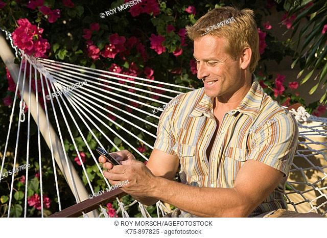 Man in hammock with cell phone
