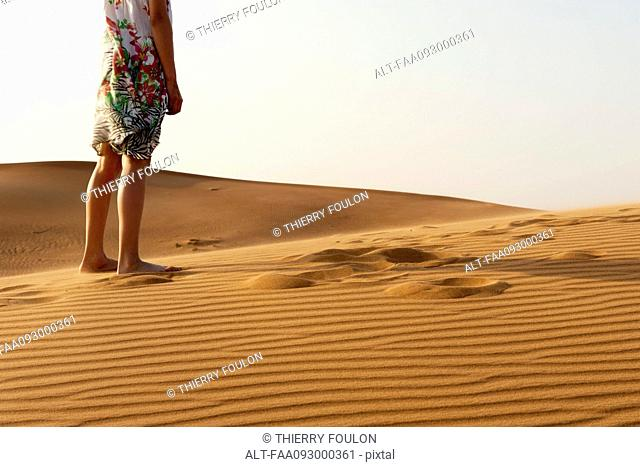 Girl standing barefoot in desert, cropped