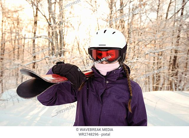 Woman in ski wear holding skis on her shoulder