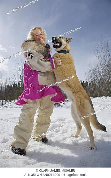 Sled dog musher, Dee Dee Jonrowe, poses with a sled dog at her home in Willow, Alaska