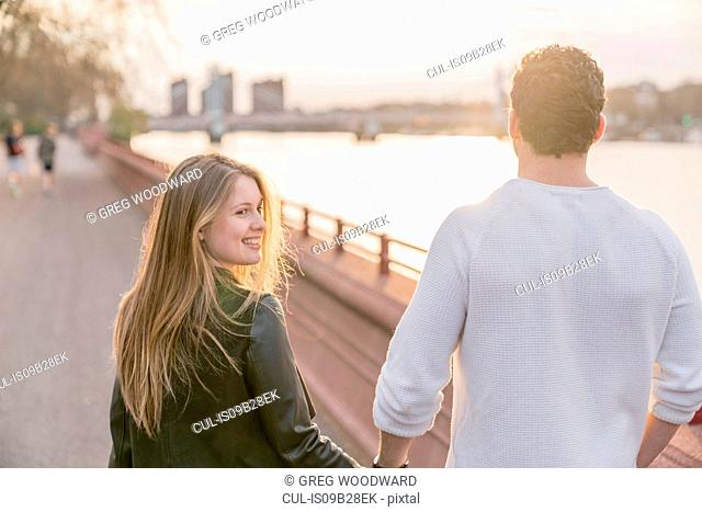 Rear view of couple strolling on waterfront at sunset, Battersea Park, London, UK