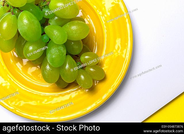 Fresh seasonal grapes in plate ready to eat On yellow background. Healthy food. Vegan food concept
