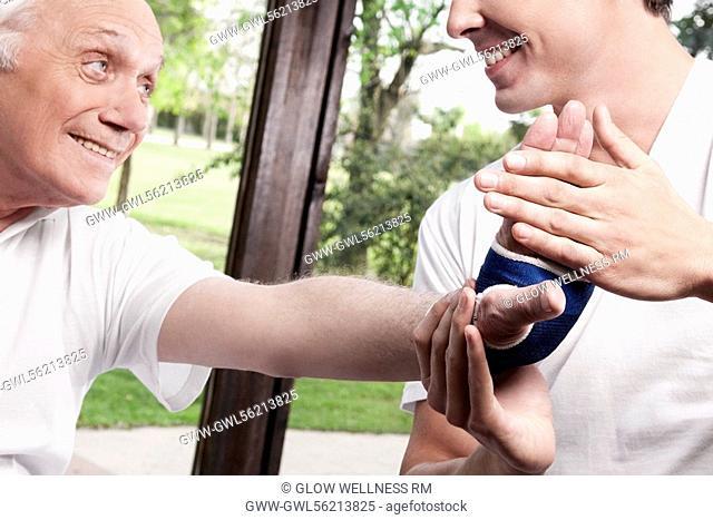 Physiotherapist examining a man's hand