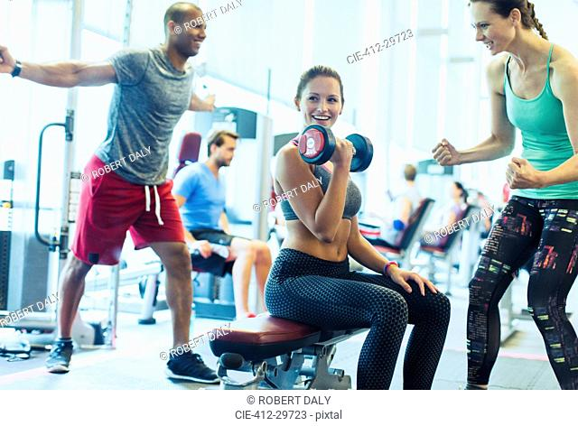 Woman cheering on friend doing dumbbell biceps curls at gym