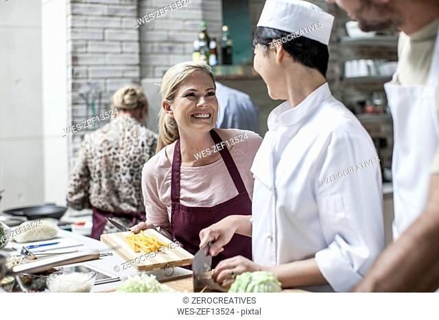 Student in cooking class smiling at female chef